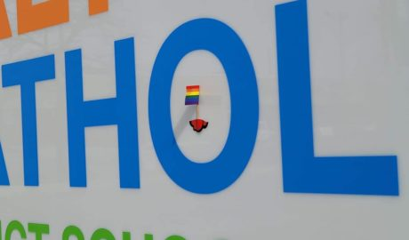 A small PRIDE flag taped to the HCDSB sign